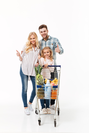 Full length portrait of a happy family standing with a shopping trolley full of groceries and showing thumbs up gesture isolated over white background