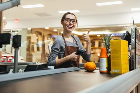 Pretty female cashier scanning grocery items at supermarket Standard-Bild