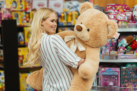 Smiling woman holding big teddy bear while standing at the supermarket Stock Photo