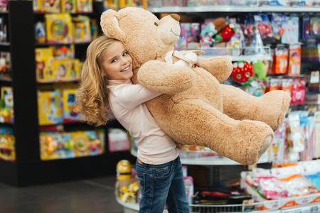 スーパーに立っている間、大きなテディベアを持つ笑顔の小さな女の子