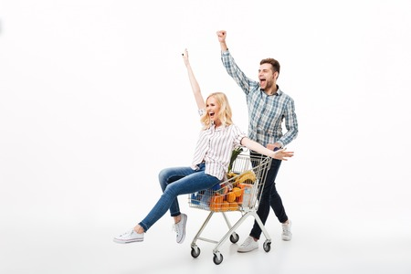 Full length portrait of a joyful couple having fun with a supermarket trolley isolated over white background Foto de archivo