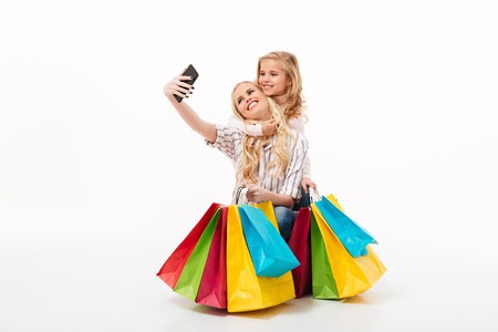 Portrait of a happy mother and her little daughter with shopping bags taking a selfie isolated over white background
