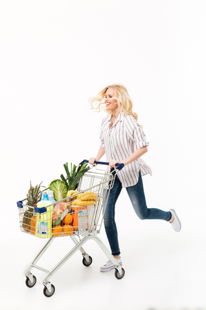 Full length portrait of a cheerful woman running with a shopping trolley full of groceries isolated over white background Foto de archivo