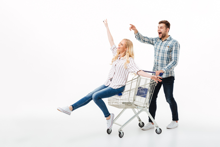 Full length portrait of a happy couple riding on a shopping trolley isolated over white background