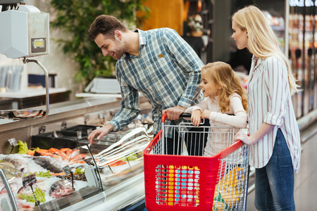 Happy family with child buying food at supermarket