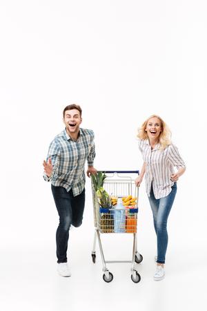 白い背景の上に隔離されたスーパーマーケットのトロリーで走っている陽気なカップルの完全な長さの肖像画