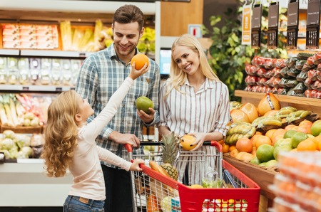 Happy young family standing with a trolley and choosing fruits at the supermarket