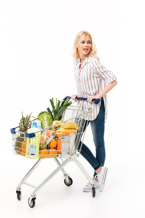 Full length portrait of a young woman standing with a shopping trolley full of groceries isolated over white background Stock fotó