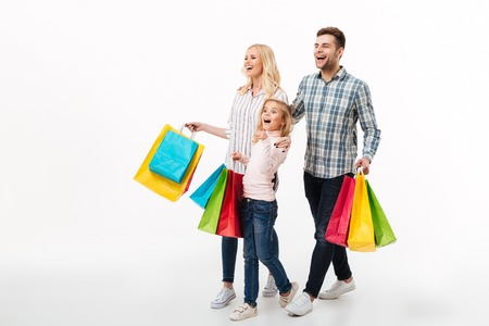 Full length portrait of a young family holding paper shopping bags while walking isolated over white background