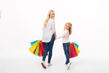 笑顔の母と小さな娘が買い物袋を持って歩き、白い背景の上に孤立した肩越しにカメラを見ている様子のバックビュー