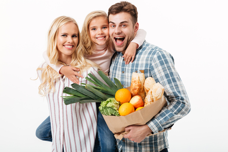 Portrait of a beautiful family holding paper shopping bag full of groceries isolated over white background 写真素材
