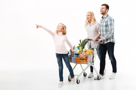 白い背景の上に隔離された食料品の完全なショッピングトロリーで歩く若い家族の完全な長さの肖像画