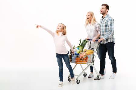 Full length portrait of a young family walking with a shopping trolley full of groceries isolated over white background
