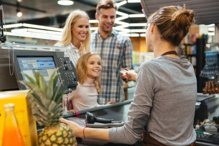 Happy family paying with a credit card to a store clerk in a supermarket