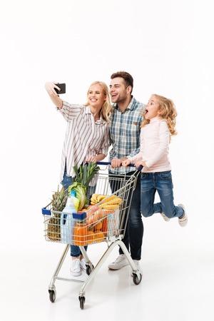 Volledig lengteportret van een vrolijke familie die zich met een het winkelen karretjehoogtepunt bevinden van kruidenierswinkels en een selfie nemen die over witte achtergrond wordt geïsoleerd