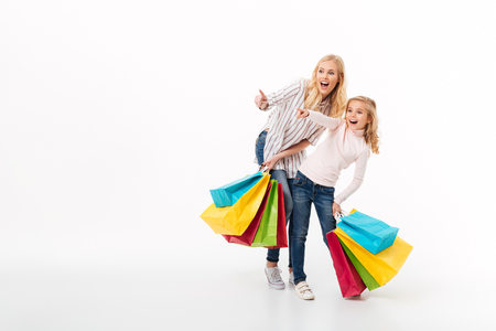 Full length portrait of a shocked mother and her little daughter standing with shopping bags and pointing fingers away isolated over white background