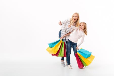 Volledig lengteportret van een geschokte moeder en haar kleine dochter die zich met het winkelen zakken bevinden en vingers richten weg geïsoleerd over witte achtergrond