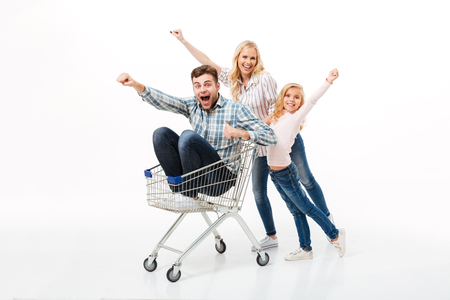 Cheery mother and her daughter giving a ride on a shopping trolley to their father isolated over white background