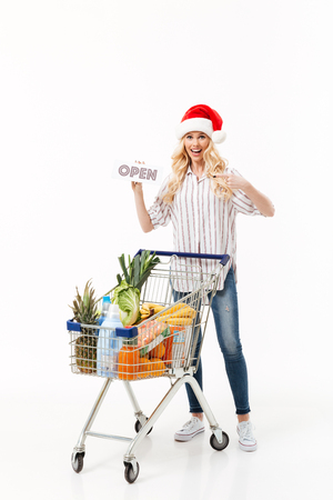 Full length portrait of a joyful woman dressed in christmas hat standing with a shopping trolley full of groceries and pointing finger at open sign isolated over white background Stock Photo