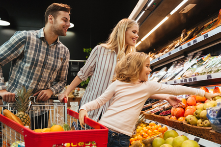 Happy family with child and shopping cart buying food at grocery store or supermark