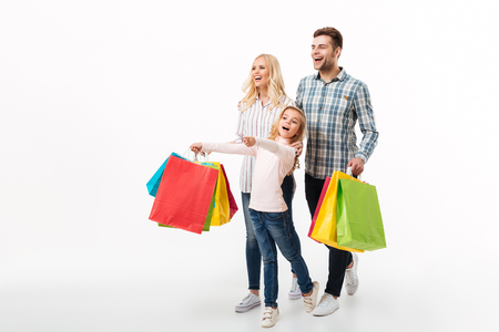 Full length portrait of a cheerful family holding paper shopping bags while walking isolated over white background Archivio Fotografico