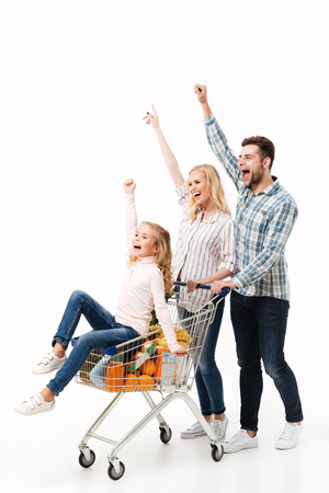 Full length portrait of a joyful family walking with a shopping trolley full of groceries isolated over white background, little girl sitting in cart