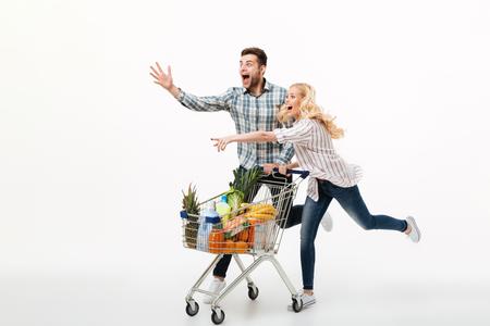 スーパーマーケットのトロリーで走り、白い背景の上に隔離された指を指している興奮したカップルの完全な長さの肖像画 写真素材