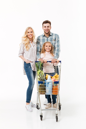 Ganzaufnahme einer fröhlichen Familie , die mit einem Einkaufswagen voll von Lebensmitteln lokalisiert über weißem Hintergrund steht