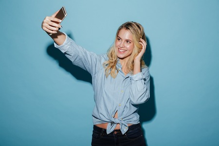 Cheerful blonde woman in shirt making selfie on smartphone over blue background