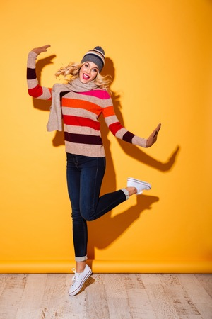 Full length portrait of smiling girl dressed in winter clothes celebrating and jumping isolated over yellow background Stock Photo
