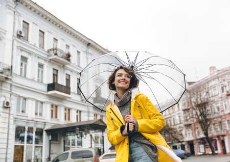 Optimistic woman in yellow raincoat and glasses having fun while walking through city under big transparent umbrella, during cold rainy day Imagens