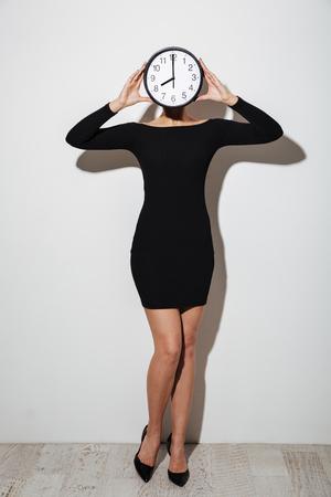 Image de femme d'affaires jeune debout isolé sur fond blanc couvrant le visage avec une horloge. Banque d'images - 93877621