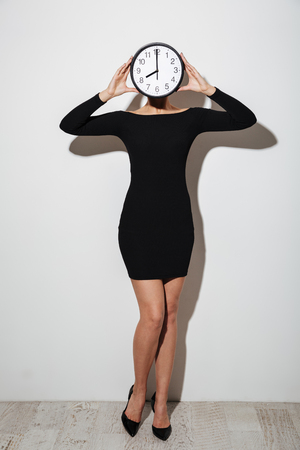 Image of young business woman standing isolated over white background covering face with clock.