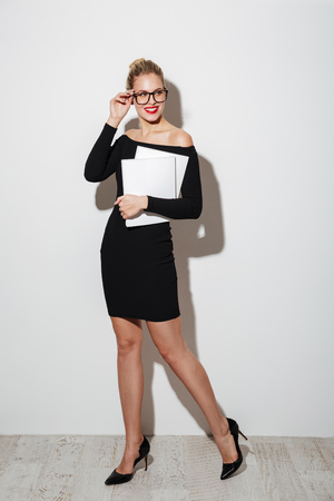 Full length image of Smiling business woman in dress and eyeglasses holding documents while looking away over gray background