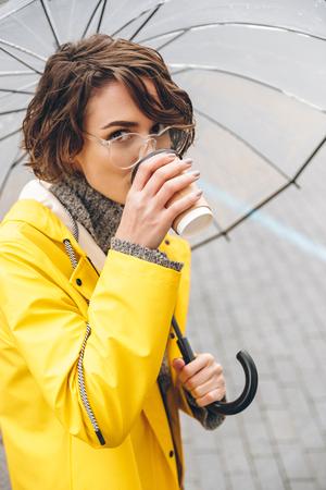 Bild der jungen Frau kleidete im Regenmantel , der draußen Kaffee trinkt . Kamera betrachtend Standard-Bild - 93861148