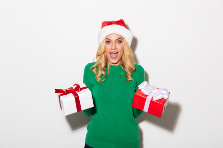 Portrait of an excited girl dressed in christmas hat holding present boxes and looking at camera isolated over white background Stock Photo