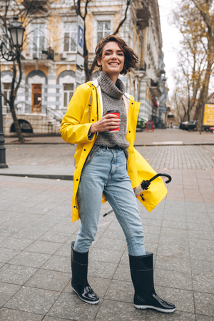 Foto van vrolijke mooie jonge vrouw, gekleed in rubberen laarzen en gele regenjas buiten lopen koffie drinken. Zoek camera. Stockfoto