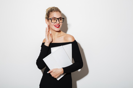 Pleased business woman in dress and eyeglasses holding documents while looking away over gray background