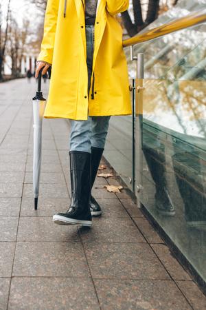 Bebouwde foto van jonge vrouw gekleed in regenjas die in openlucht loopt. Stockfoto