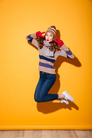 Full length portrait of cheery girl dressed in winter clothes celebrating and jumping isolated over yellow background