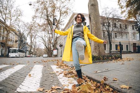 レインコートとゴムブーツを着た笑顔の少女が脇を見て屋外を歩いている姿。