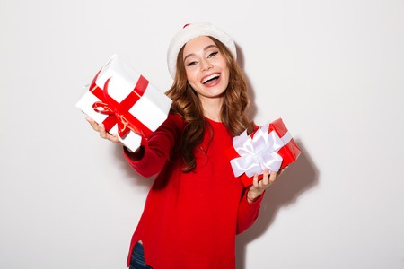 Portrait of a smiling girl dressed in christmas hat giving present boxes and looking at camera isolated over white background