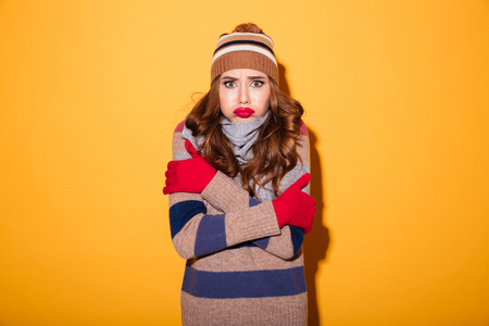 Portrait of an upset frozen girl dressed in winter clothes looking at camera isolated over yellow background