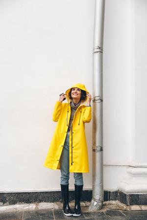 Satisfied adult girl 20s wearing yellow coat standing with hood on looking up, enjoying rainy weather with smile