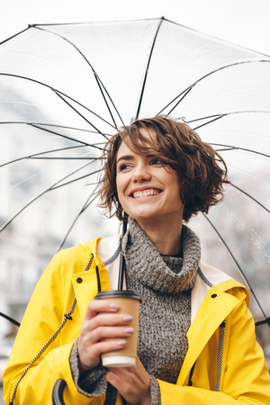 Image of cheerful young woman dressed in raincoat walking outdoors drinking coffee. Looking aside.