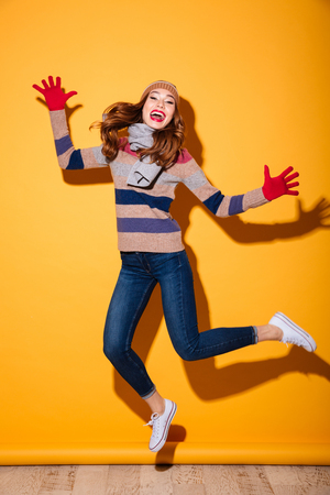 Full length portrait of happy girl dressed in winter clothes celebrating and jumping isolated over yellow background Stock Photo