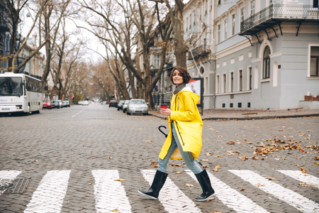 Image of a smiling girl dressed in raincoat and rubber boots walking outdoors looking aside.