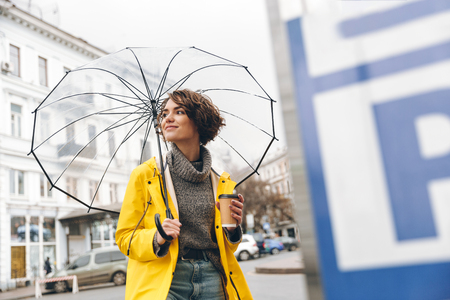 Stylish woman in yellow raincoat walking through urban area under big transparent umbrella, holding takeaway coffee in hand Stok Fotoğraf