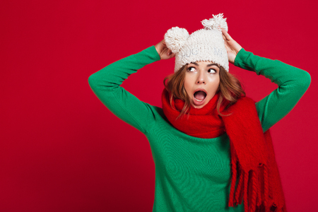 Shocked brunette woman in sweater, funny hat and scarf holding head while looking away over red backgroun