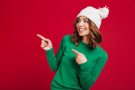 セーターと面白い帽子で笑顔のブルネットの女性は、赤い背景を指し、遠ざかって